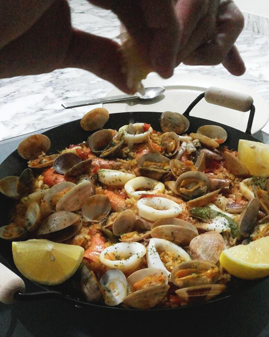 Squeeze 2 slices of the lemon wedges on the paella